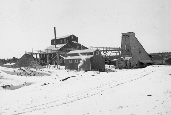 Black and white photograph of a machine and shaft house in the winter.