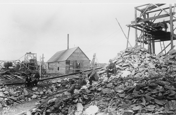 Photograph of a group of men sitting on rock piles and buildings in Goldenville.