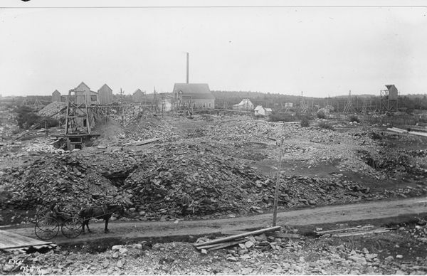 Photograph of buildings and mine structures surrounded by piles of discarded rocks.
