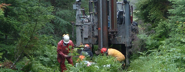 Workers on a drill rig collect soil and rock samples in the woods.