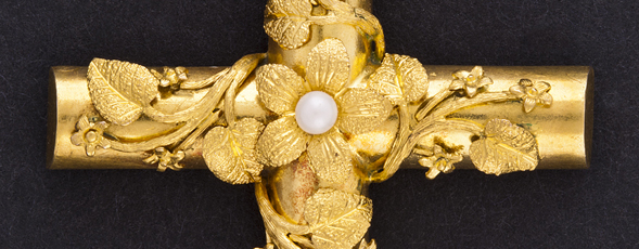 Detail of a gold cross-shaped pendant with mayflowers twining around it and a pearl in the centre-most flower.