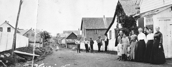 People gathered on a street of houses in Goldenville, NS.
