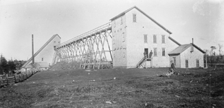 Photograph of a stamp mill and shaft house connected by an elevated rail.