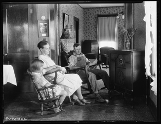 A photograph of a family sitting around a radio in the 1930s.