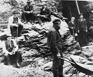 Black and white photo of a gold miner at the entrance to an adit at the Waverley Gold District.
