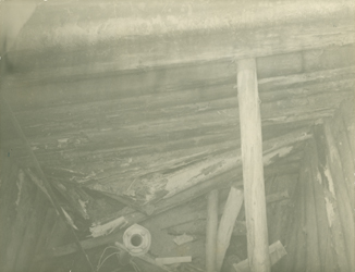 Black and white photograph of broken timbers and debris fill a wood-lined shaft.
