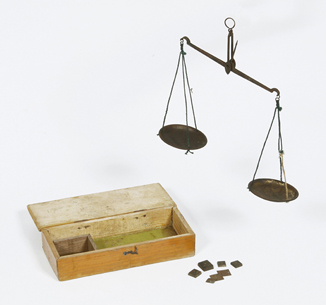 Photograph of an historic hanging balance scale, weights and wooden storage box.