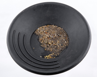 Image of a black pan with gravel and gold in it, illustrating how gold is separated from the gravel using the panning method.