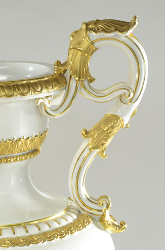 Detail of the side and handle of a white porcelain urn with decorative gilt trim.