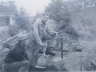 Black and white photograph of two men next to a flat stone that was once the base for an arrastre.