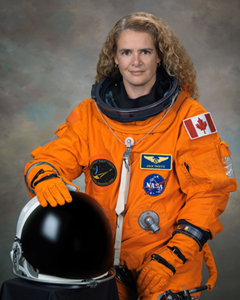 Photograph of Canadian astronaut Julie Payette in her flight suit, next to her helmet.