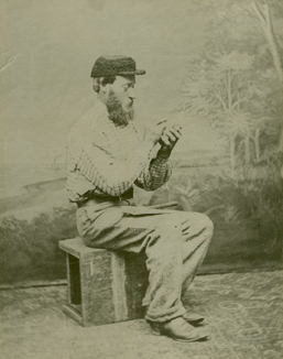 Studio photograph of John Gerrish Pulsifer against a landscape backdrop painted by Frederick B.Nichols