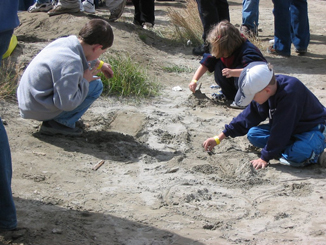 Children playing with toy cars in tailings sand.