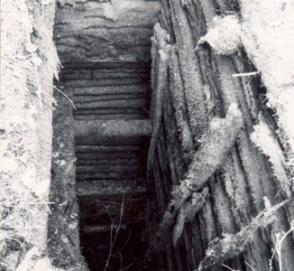 Black and white photograph of an abandoned mine shaft.