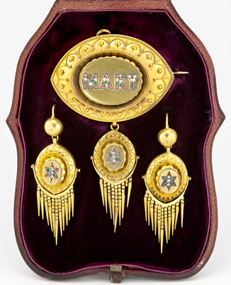 "Large gold brooch and earring set with the name ""Mary"" set in stone on the brooch."