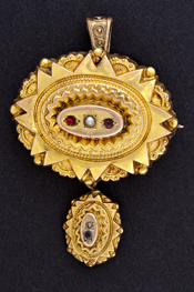 Oval gold brooch set with garnets.