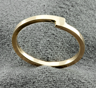 Gold band ring where the ends overlap instead of meeting in the centre.